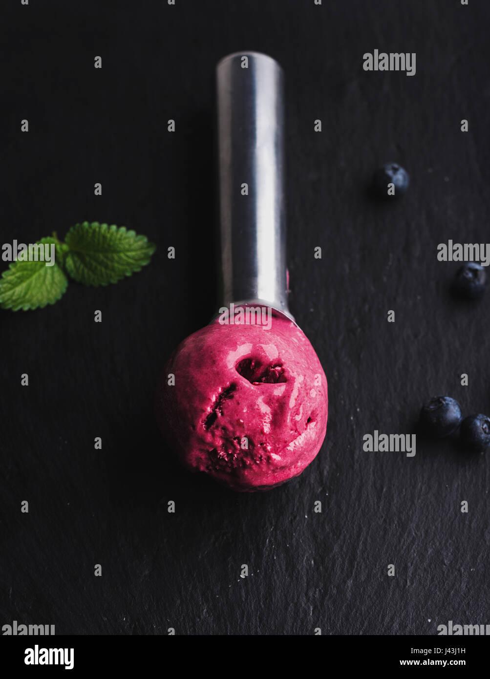 Blueberry ice-cream scoop over black slate stone background - Stock Image