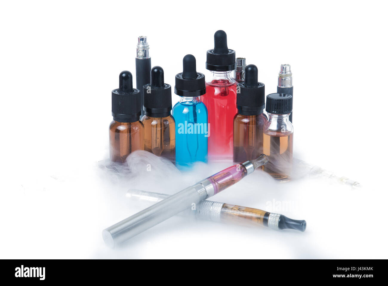 Thin e-cigarettes with glass bottles and smoke on white background - Stock Image