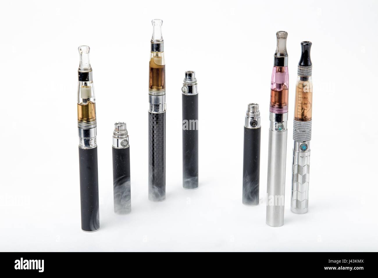 Thin e-cigarettes and smoke on white background - Stock Image