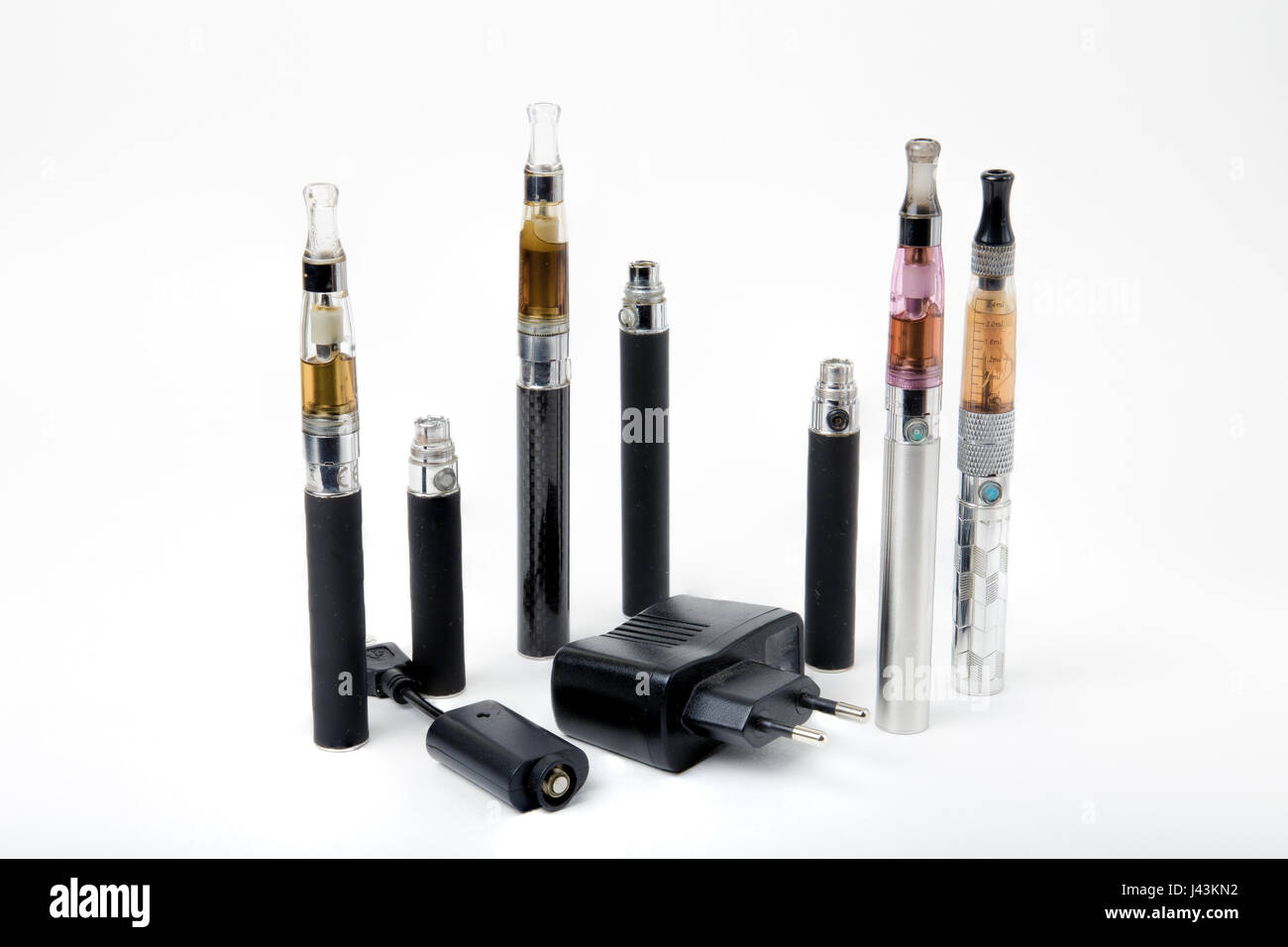 Thin e-cigarettes with charger and smoke on white background - Stock Image