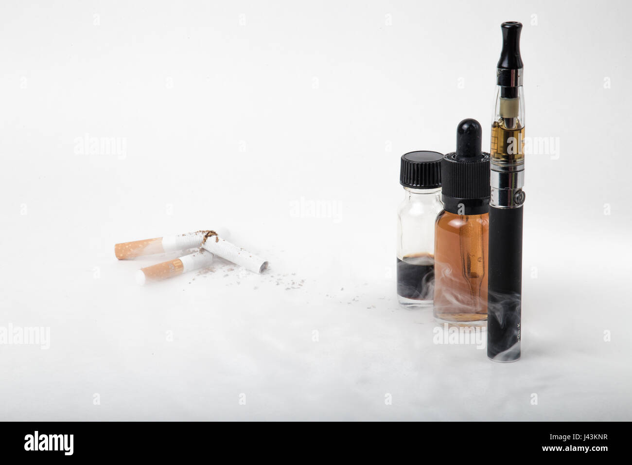 Electronic cigarette with 2 e-liquids and pile of broken tobacco smokes - Stock Image
