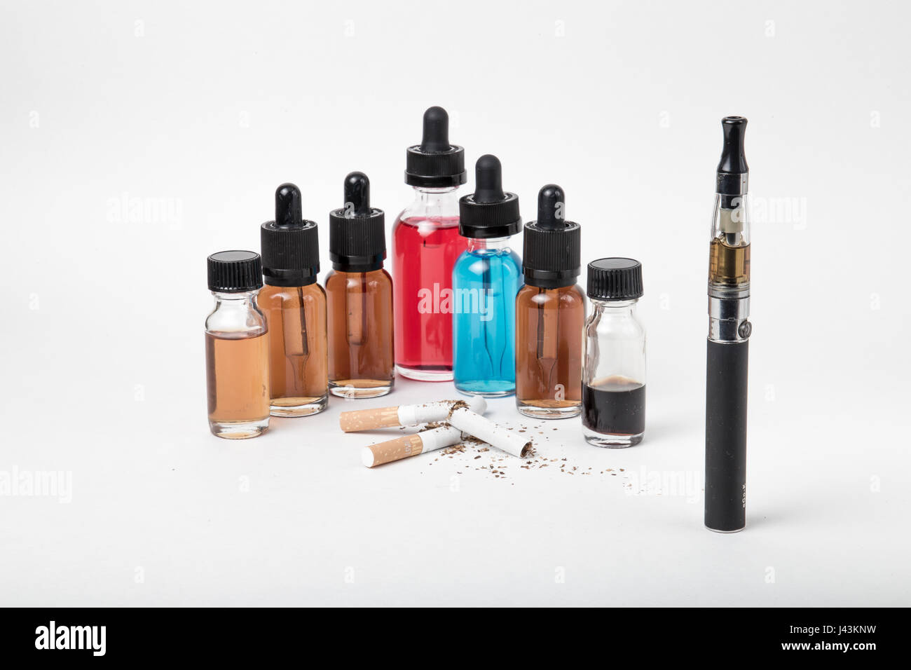Many bottles of e-juice and vaporizer and pile of tobacco cigarettes - Stock Image