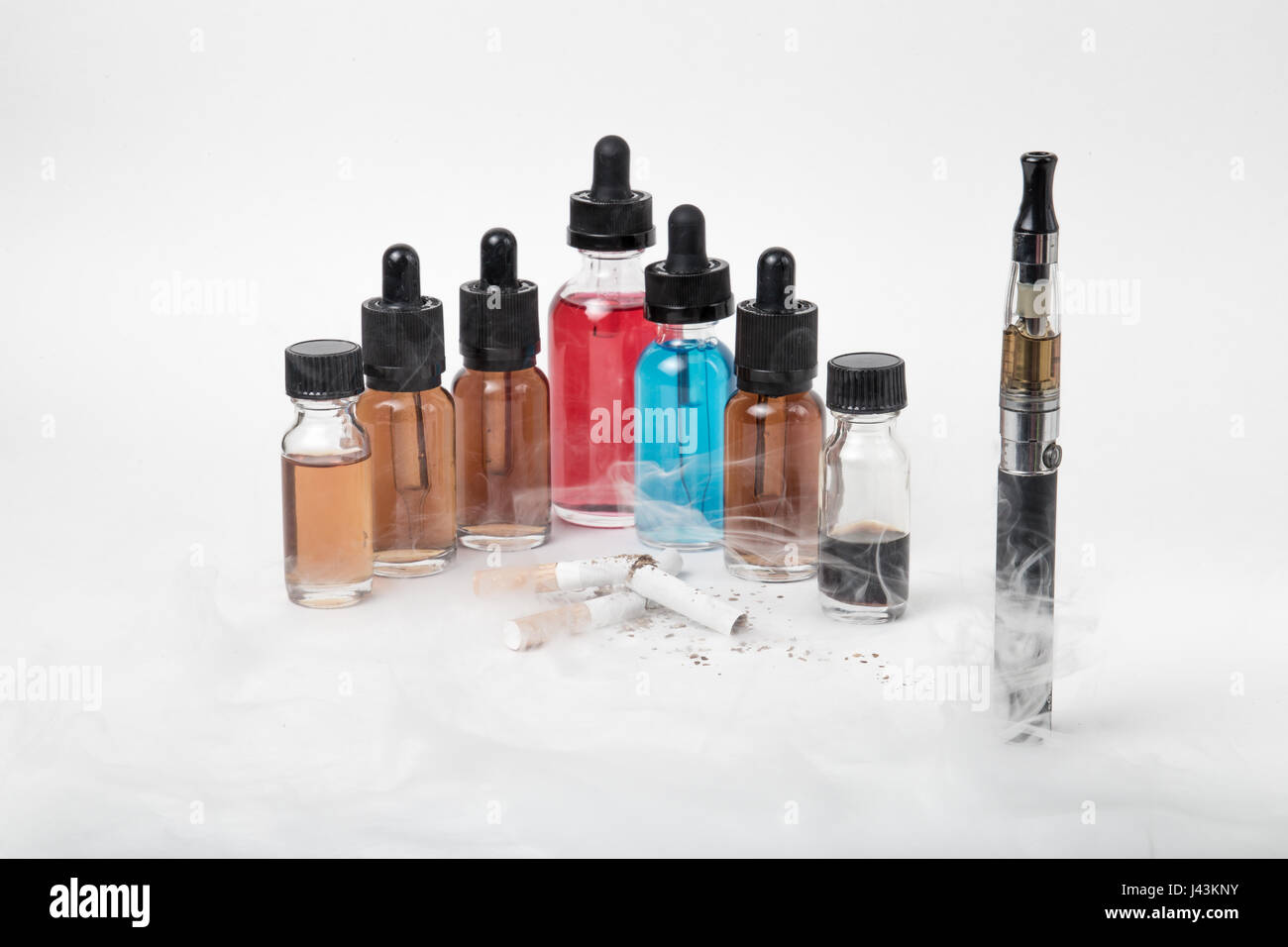Many bottles of e-juice and vaporizer with lots of smoke - Stock Image