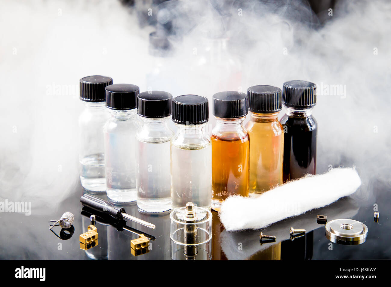 Vaporizer smoke with juice bottles, screwdriver and cotton wick with tools - Stock Image
