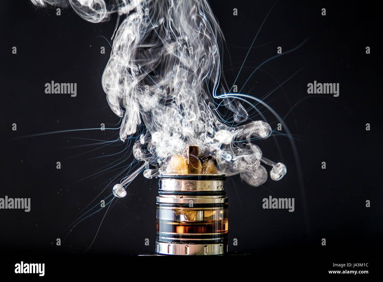 Vaporizer smoke explosion on isolated black background in studio - Stock Image