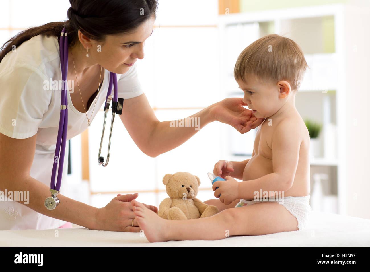 Doctor paediatrician checking boy's neck - Stock Image