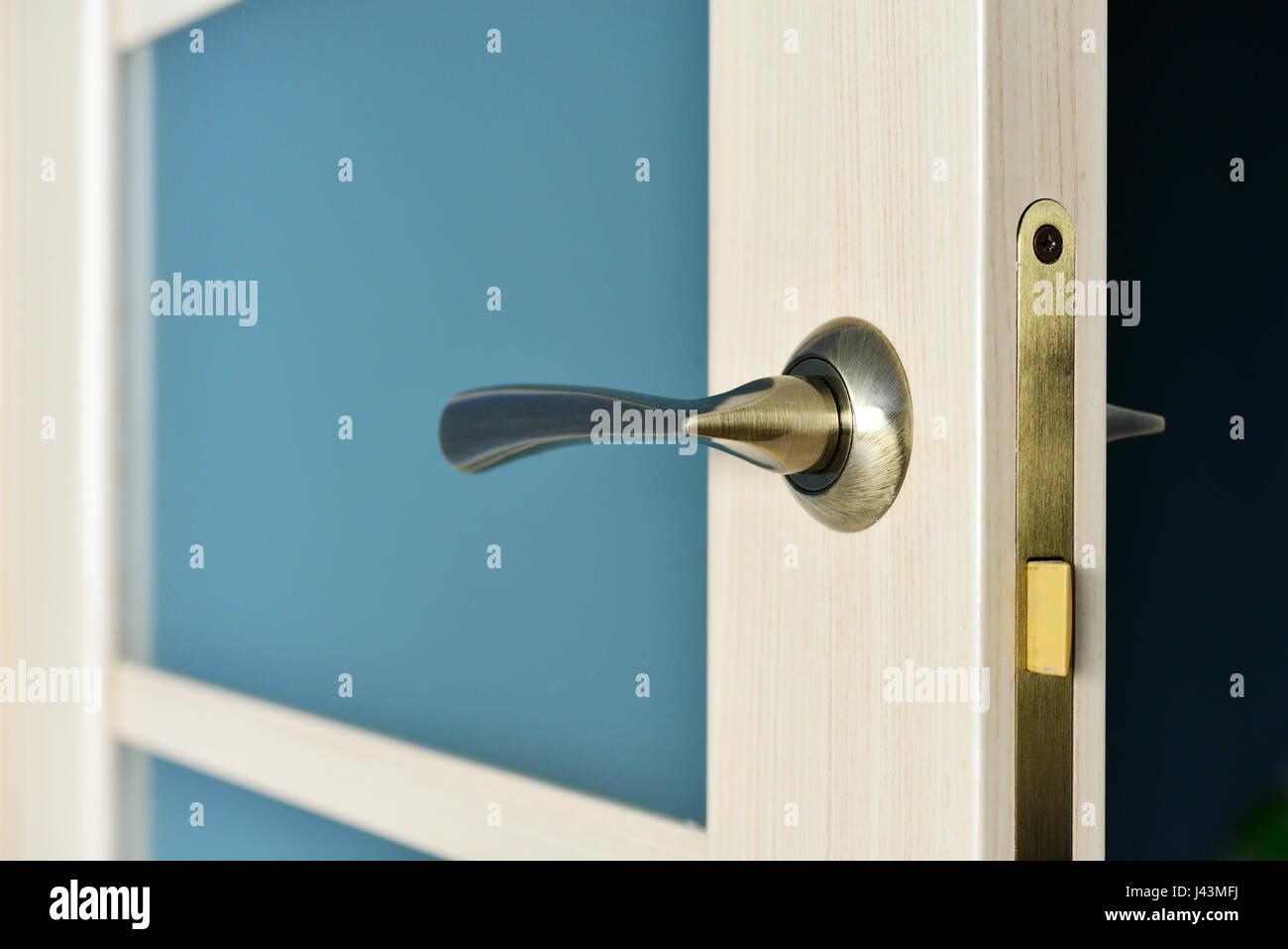 Modern style bronze door handle on natural wooden interior doors with glass - Stock Image