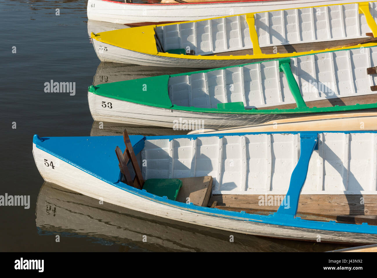 Brightly Coloured Wooden Canoes Moored In Evening Sun At The Meare