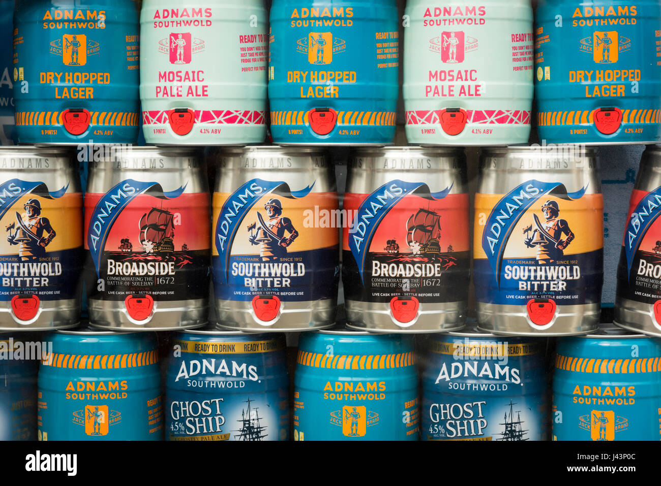 Metal barrels of beer brewed by the Adnams Brewery Suffolk piled up in a shop windoe - Stock Image