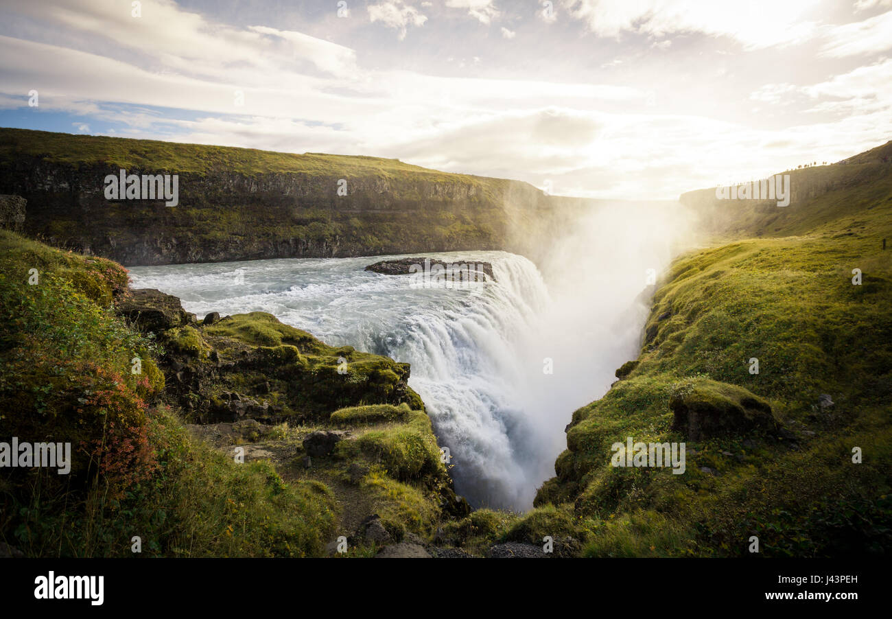 Cold water in Iceland. Waterfall in rocky mountains. Fresh and green grass. Beautiful mountain range in the background. - Stock Image
