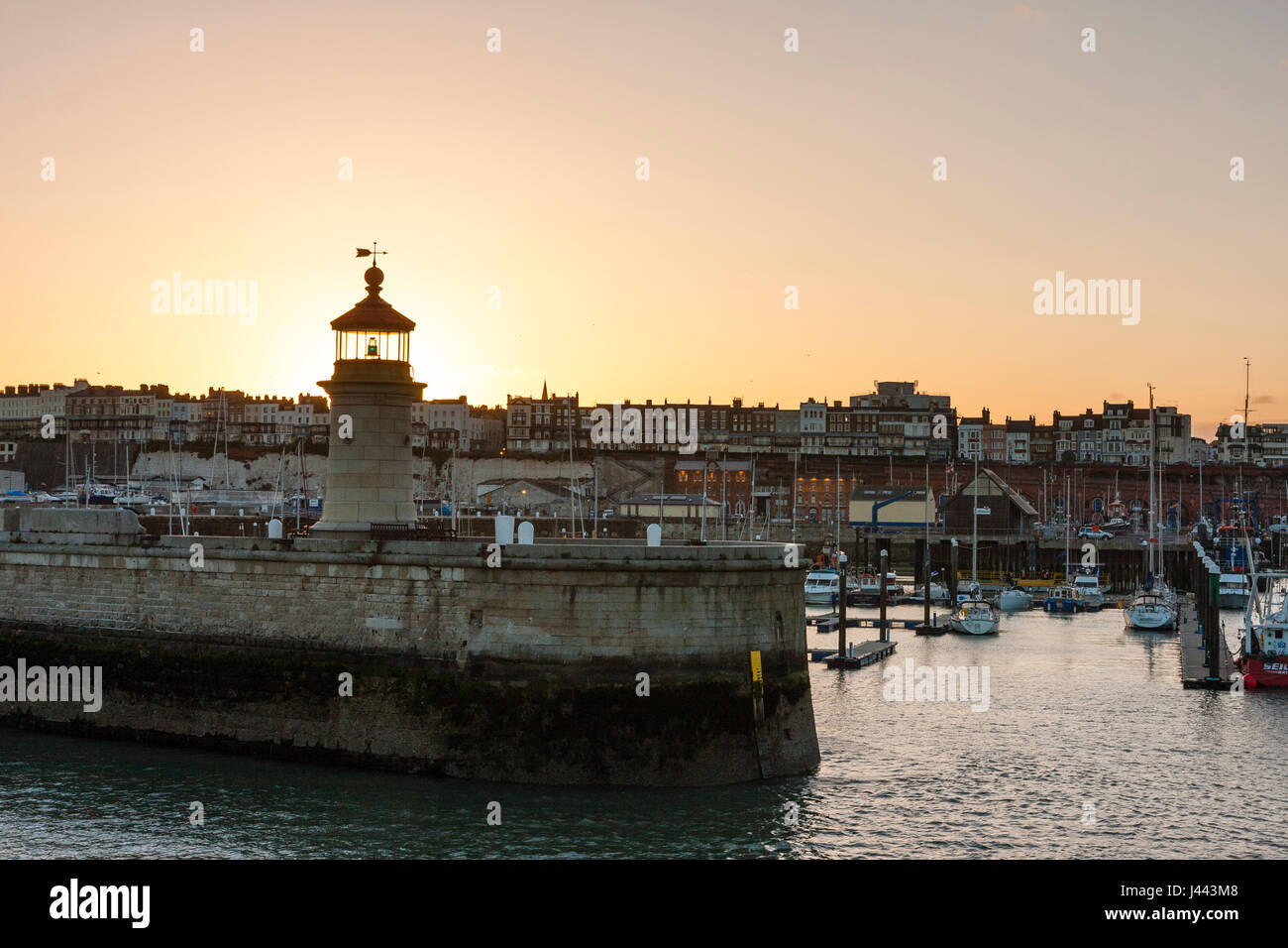 Ramsgate Royal Harbour. Lighthouse at end of jetty with boats moored in the harbour and behind that Ramsgate seafront Stock Photo