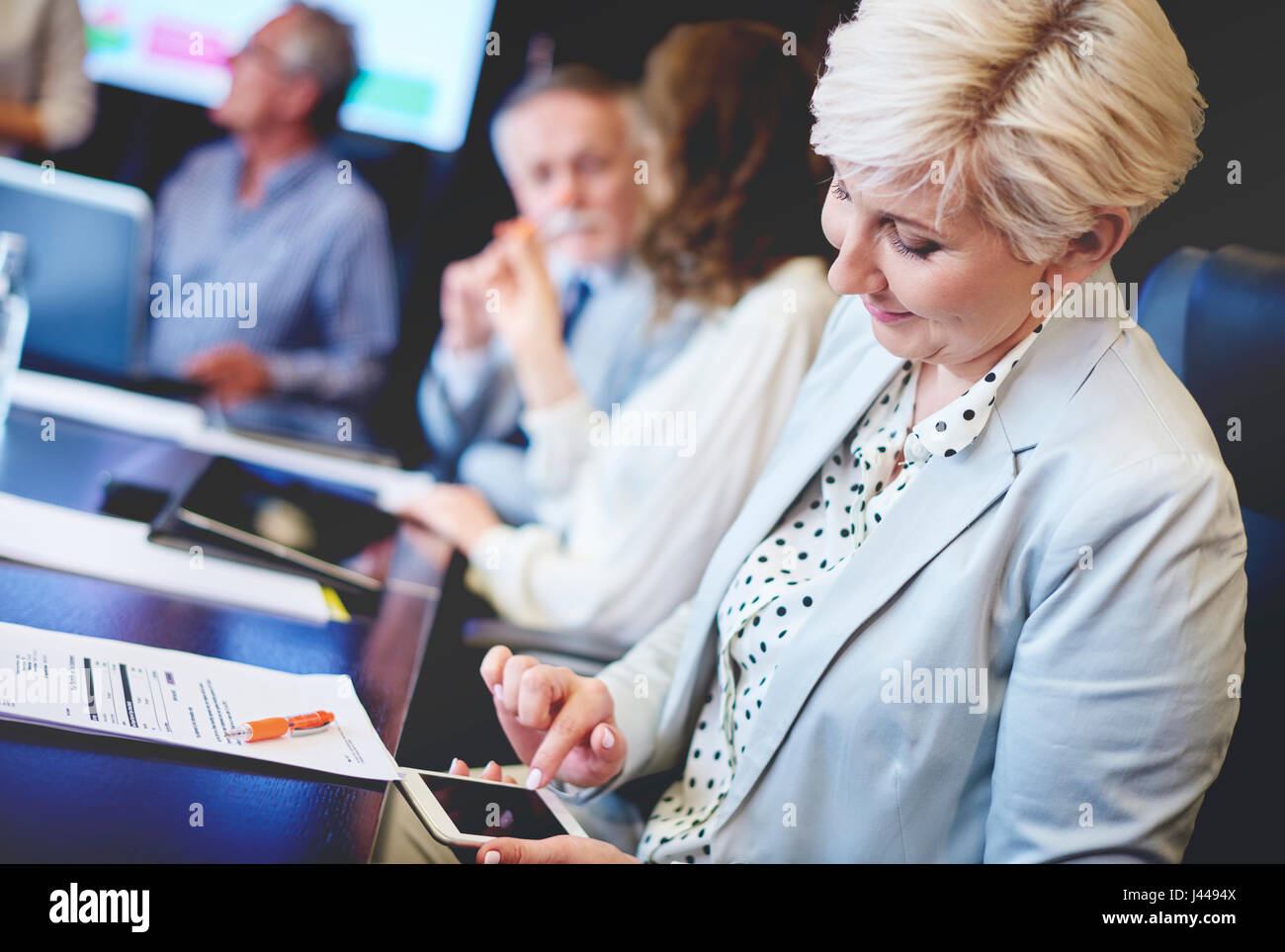Female coworker using cell phone - Stock Image