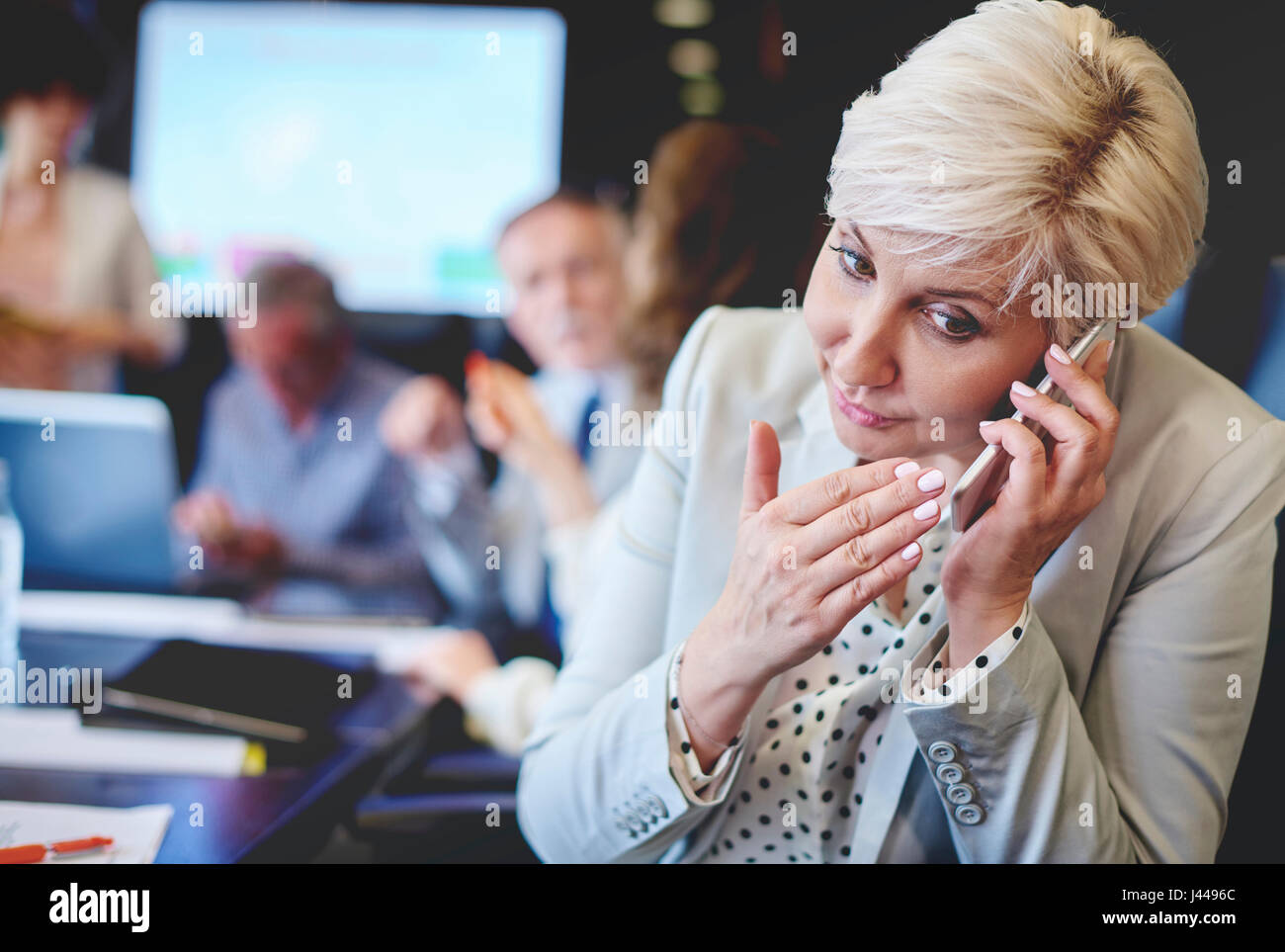 Urgent phone call while having meeting - Stock Image