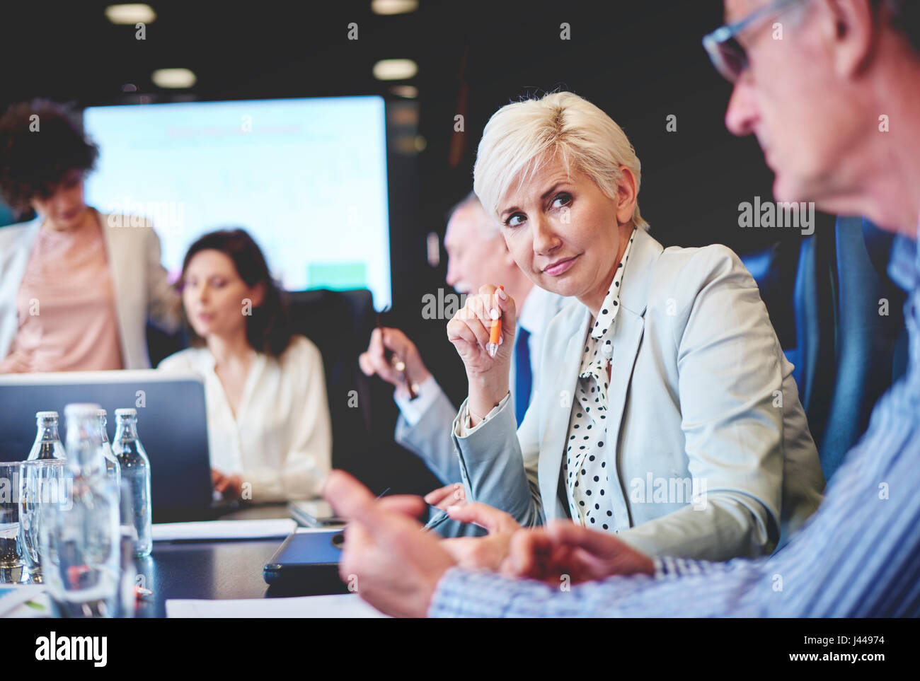 Pensive woman listening to colleagues opinion - Stock Image