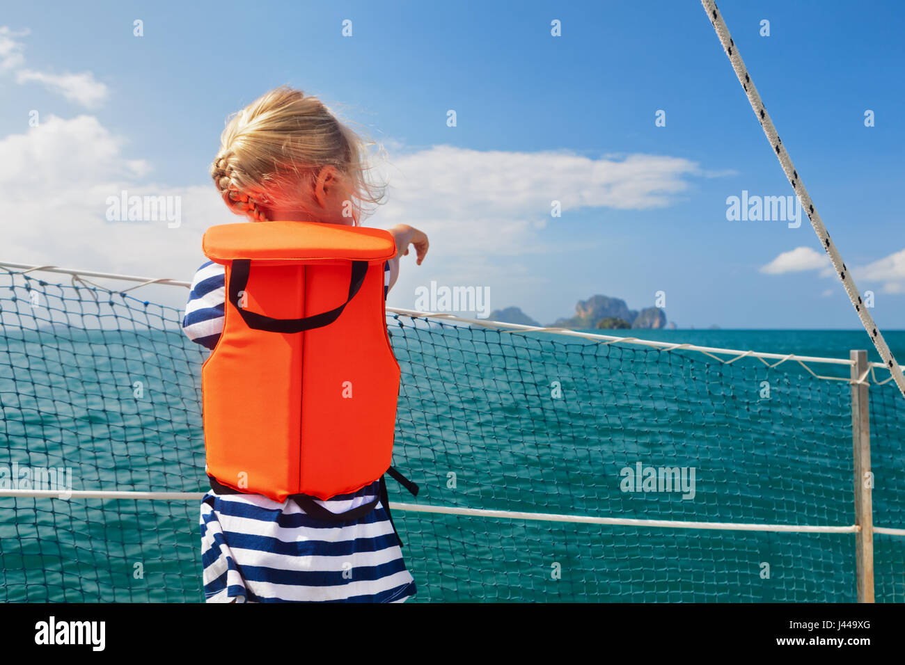 Happy little baby in life jacket on board of sailing boat watching offshore sea and tropical islands on summer cruise. - Stock Image