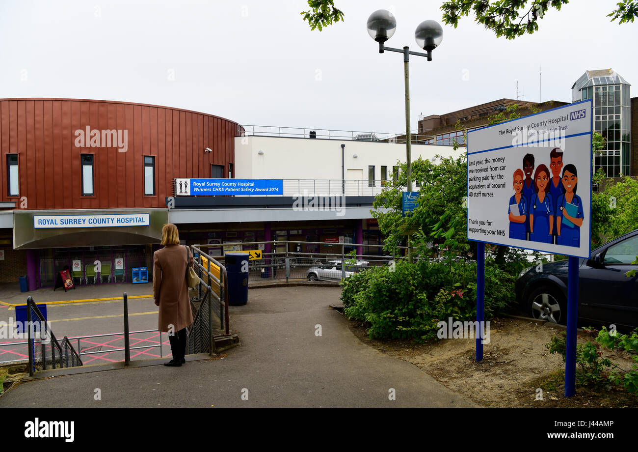 General view of facade of Royal Surrey County Hospital, with sign justifying its car parking charges, Guildford, - Stock Image
