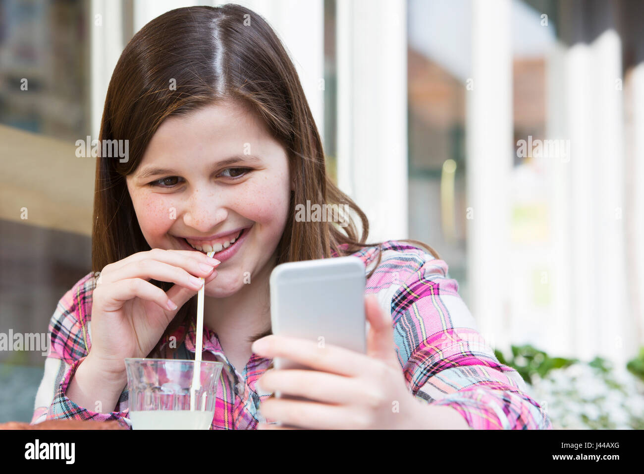 Young Girl At Cafe Reading Text Message On Mobile Phone - Stock Image