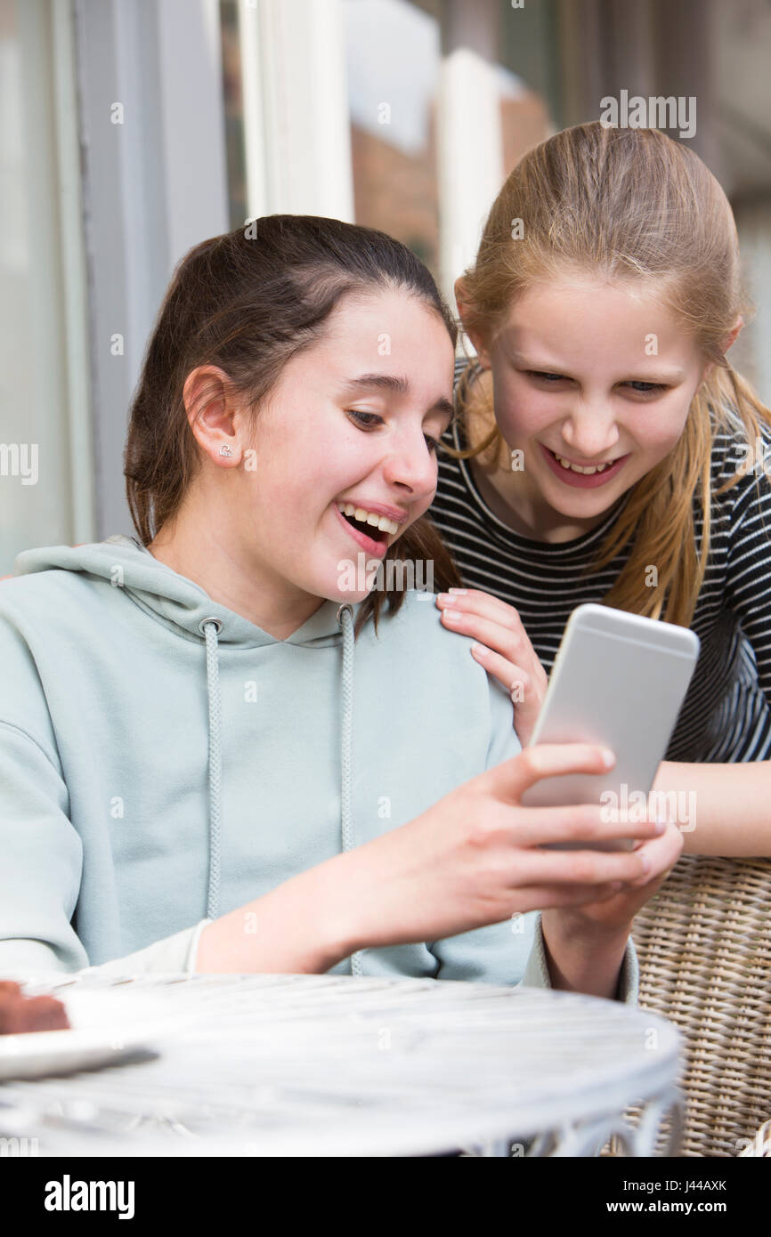 Two Young Girls At Cafe Reading Text Message On Mobile Phone - Stock Image
