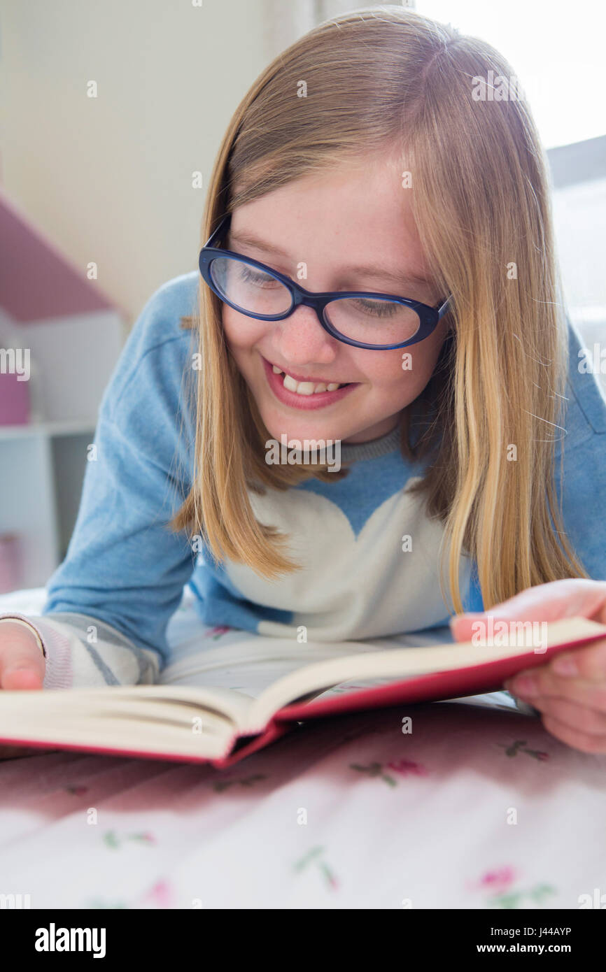 Young Girl Lying On Bed Reading Book - Stock Image