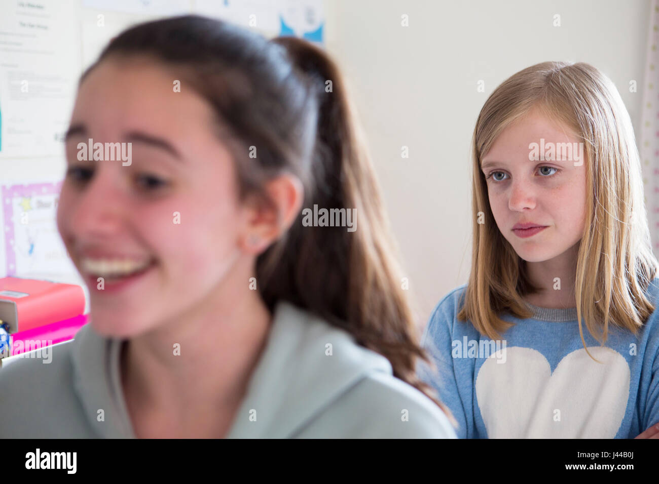 Young Girl Staring At Disliked Friend - Stock Image