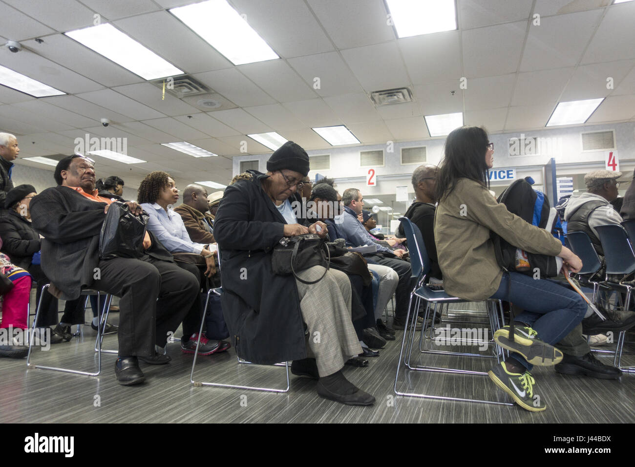 People wait to take care of business at their local social security office in Brooklyn, New York. - Stock Image