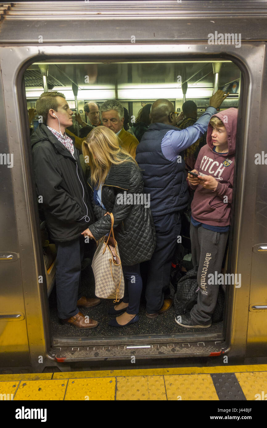 Evening rush hour at the 42nd Street subway station below Grand Central Terminal is always a shoulder to shoulder - Stock Image