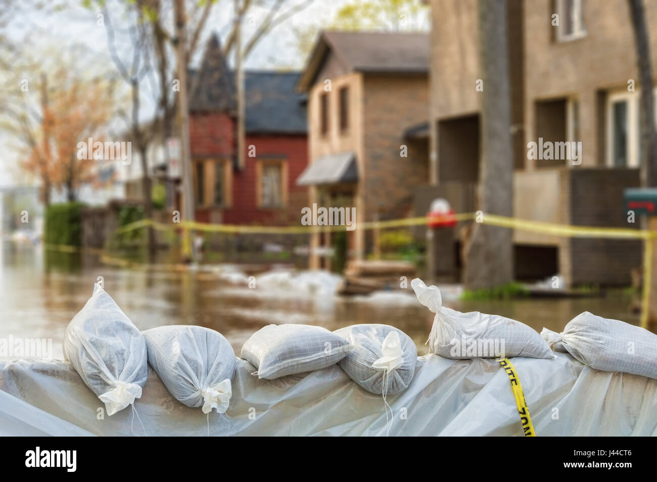 Close shot of flood Protection Sandbags with flooded homes in the background Stock Photo