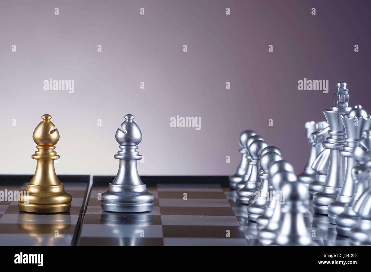Golden bishop facing silver bishop chess on gradient background - leadership, team, successful and business concept - Stock Image