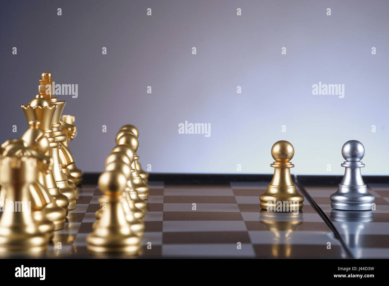 Golden pawn facing silver pawn set of chess on gradient background - leadership, team, successful and business concept - Stock Image