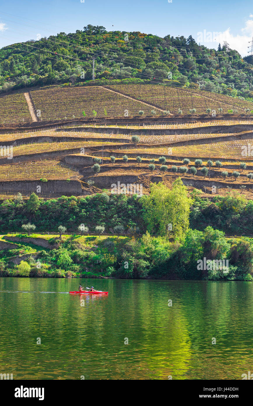 Portugal Douro Valley, a canoe carrying two people heads up the Douro River Valley near the port wine town of Pinhao, - Stock Image