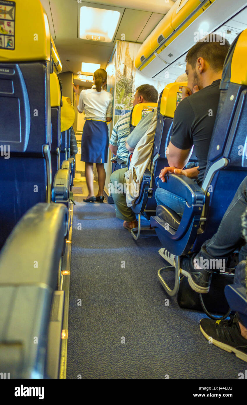 Air hostess on Ryanair flight doing safelty demonstration as passengers watch - Stock Image