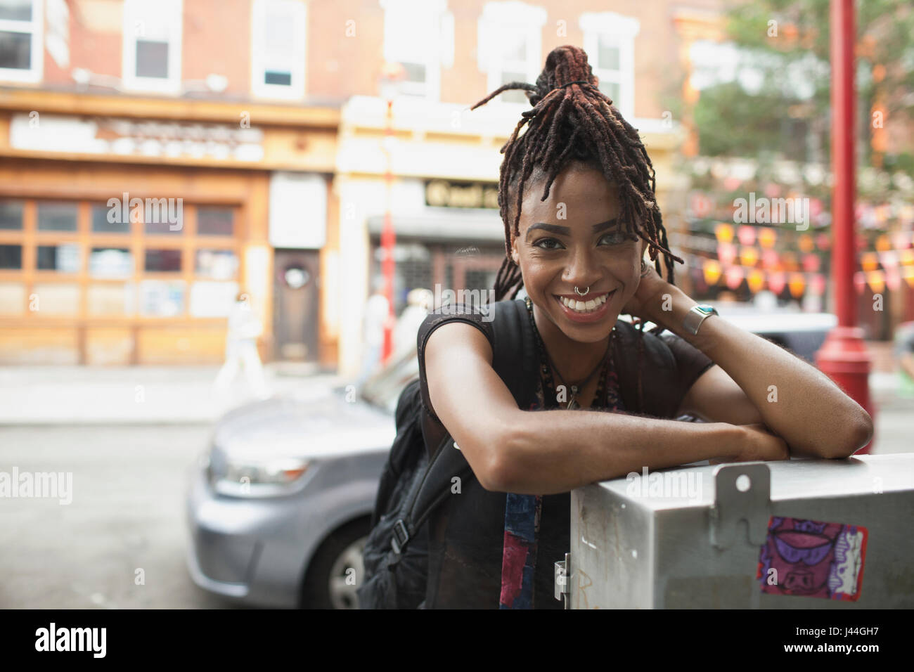 A young woman leaning against a metal box. - Stock Image