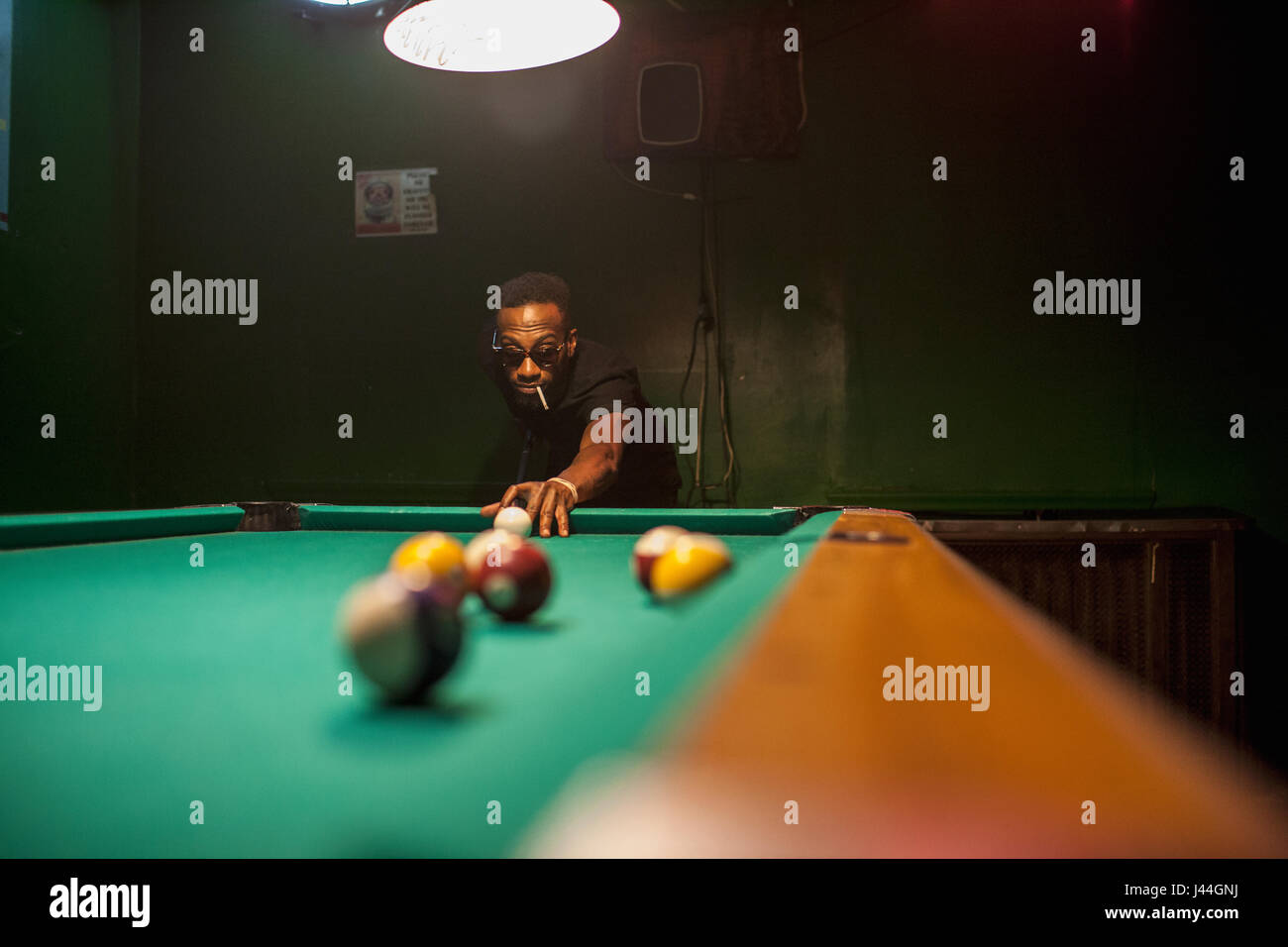 A young man playing pool. - Stock Image