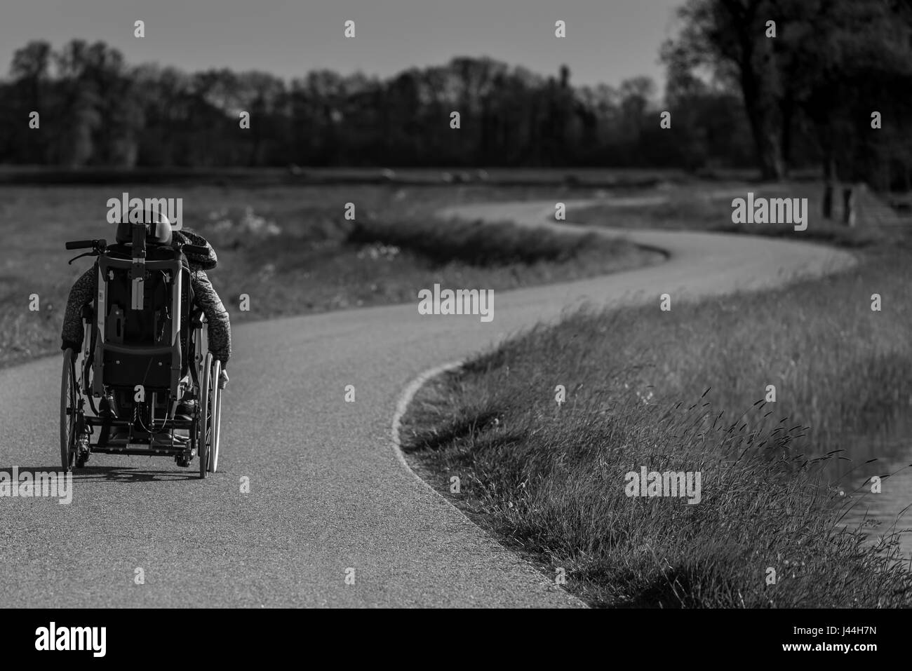 A disabled person in a wheelchair alone on a winding road - Stock Image