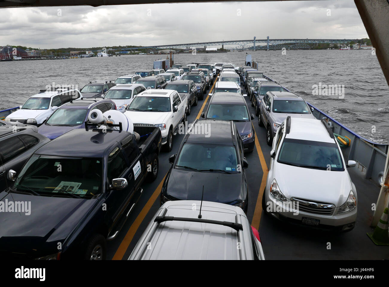 Cars on the Cross Sound Ferry leaving New London for Orient Point Long Island. The bridge is route I 95. - Stock Image