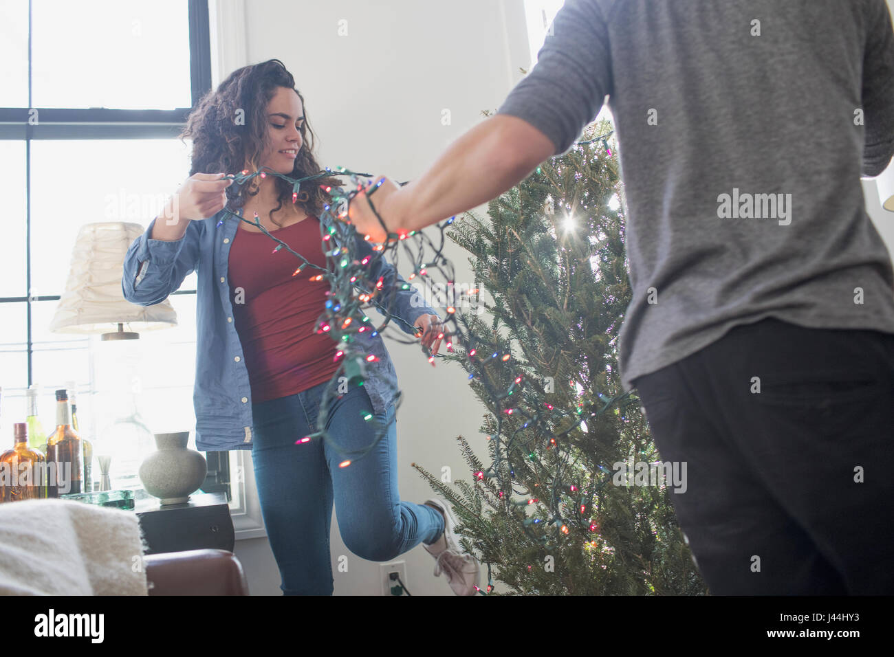 A young woman and man decorating a Christmas tree Stock Photo