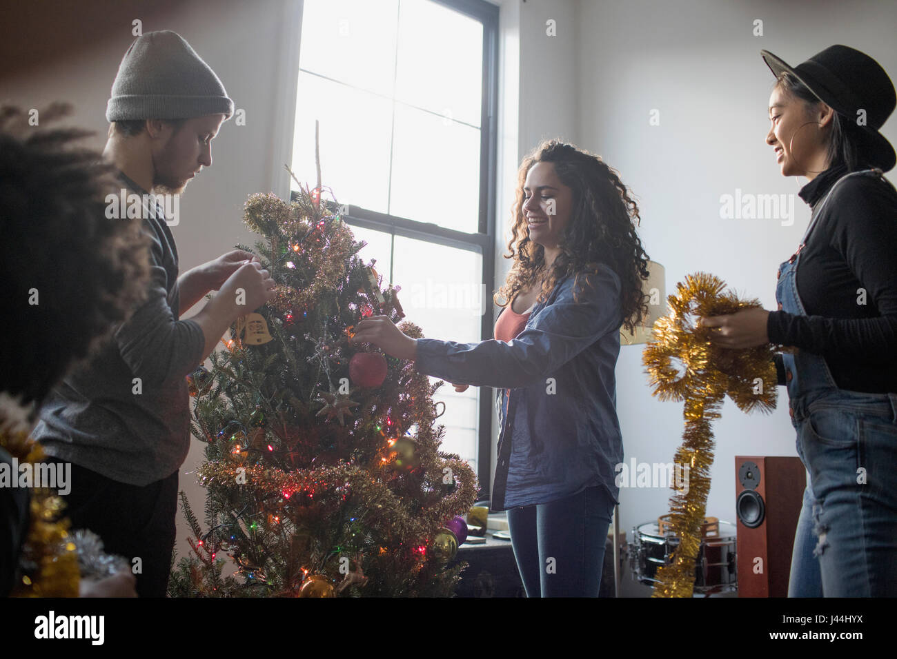 A group of people decorating a Christmas tree Stock Photo