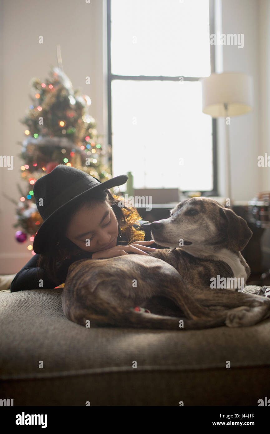 A young woman with a dog on a couch - Stock Image