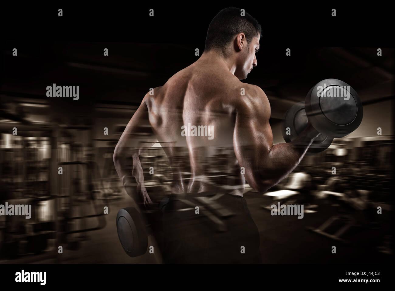 Athletic man training biceps on gym background Stock Photo