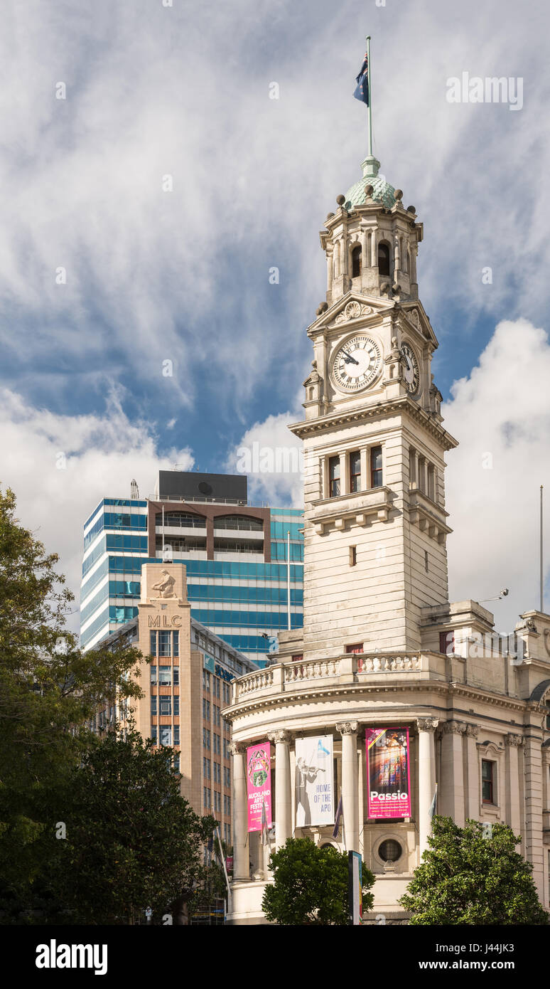Auckland, New Zealand - March 4, 2017: The white stone Clock Tower of town hall with theater posters and flag. Green - Stock Image