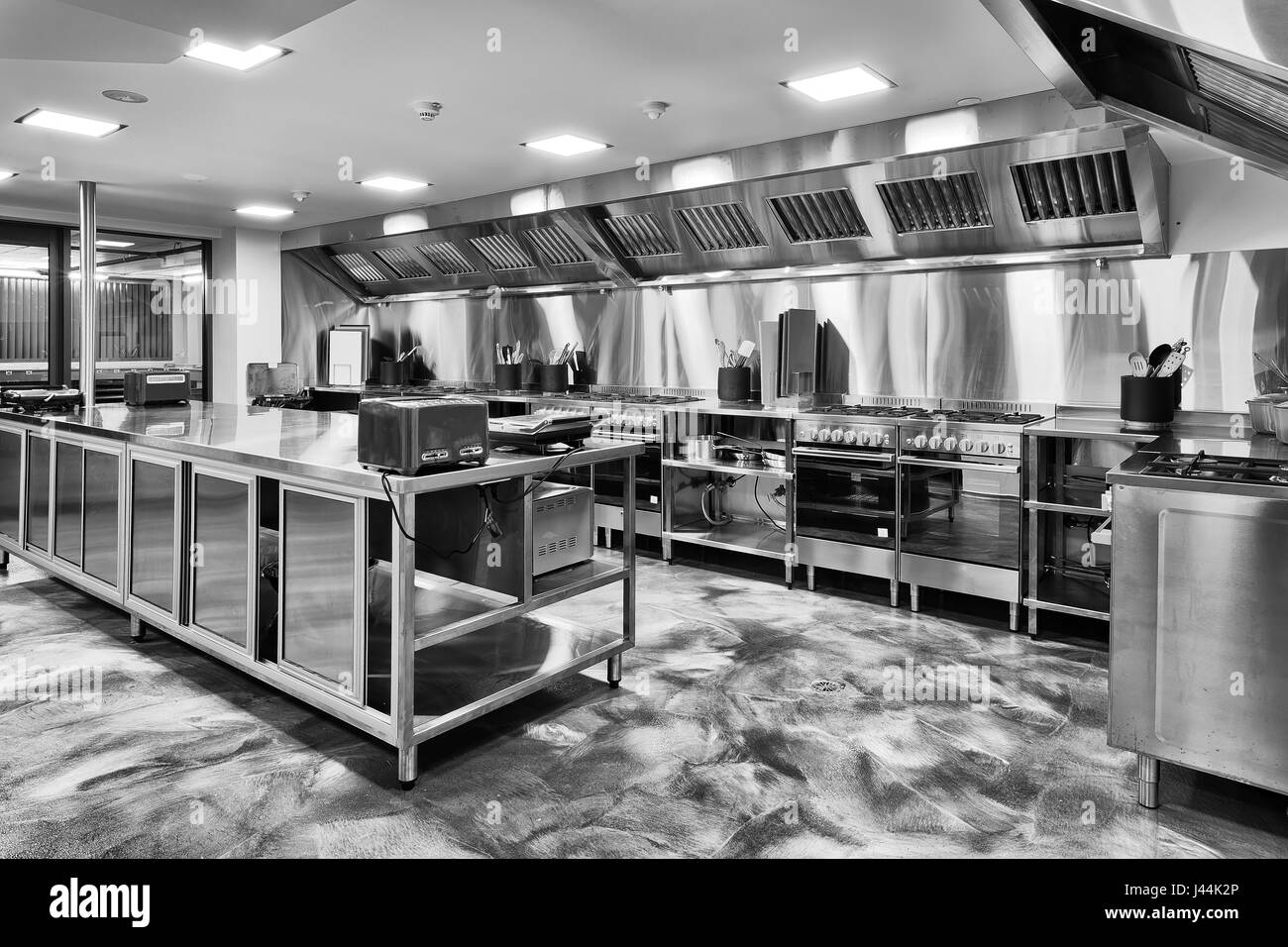 Modern brand new kitchen fully equipped with gas ovens, utensils, cooking table tops and appliences in black-white. - Stock Image