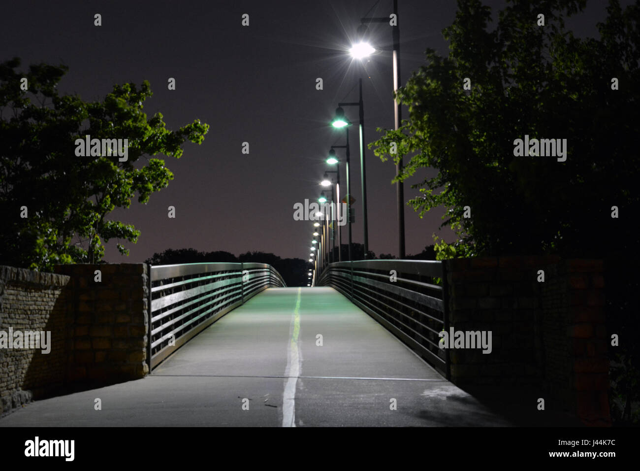 Lights illuminate the Mockingbird footbridge at night at the northern end of White Rock Lake in Dallas, Texas - Stock Image