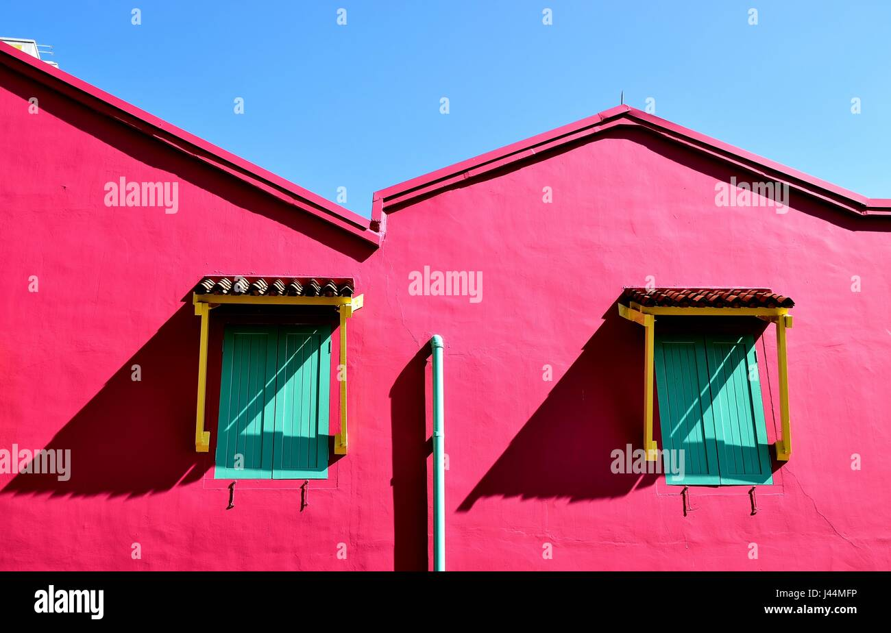 Bold pink exterior of a traditional Singapore shop house with wooden ...