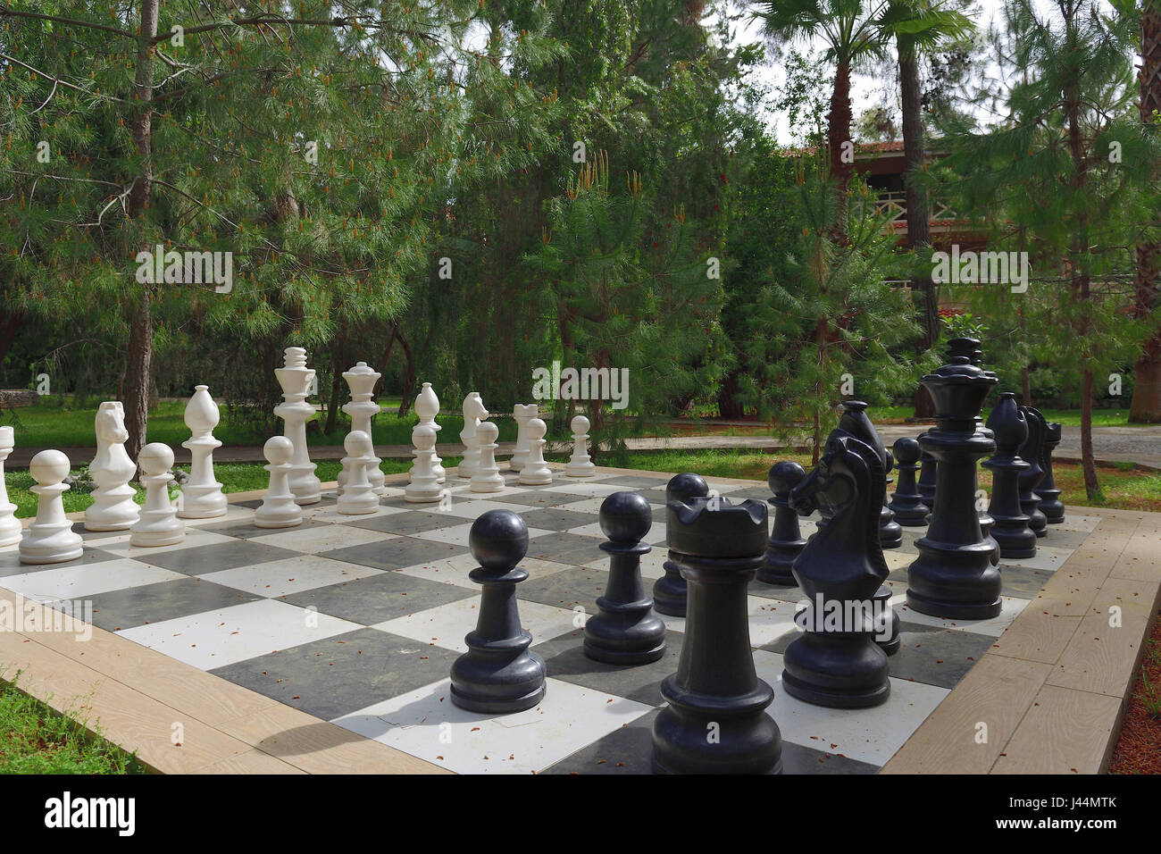 Large chess set outdoors on lawn - Stock Image