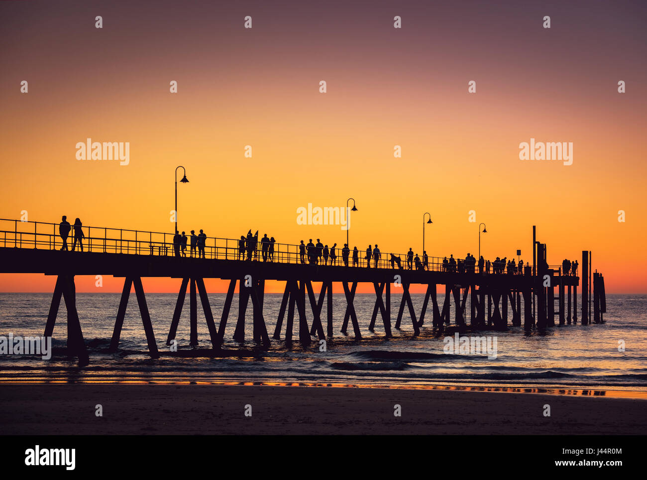 Glenelg beach jetty with people at sunset, Adelaide, South Australia - Stock Image