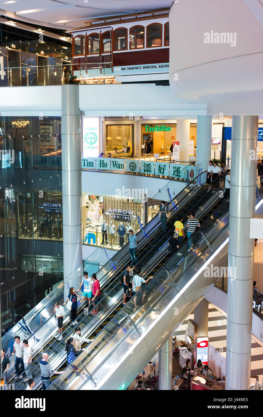 Escalators, people and shops in Siam Center, a large shopping mall in Bangkok. - Stock Image
