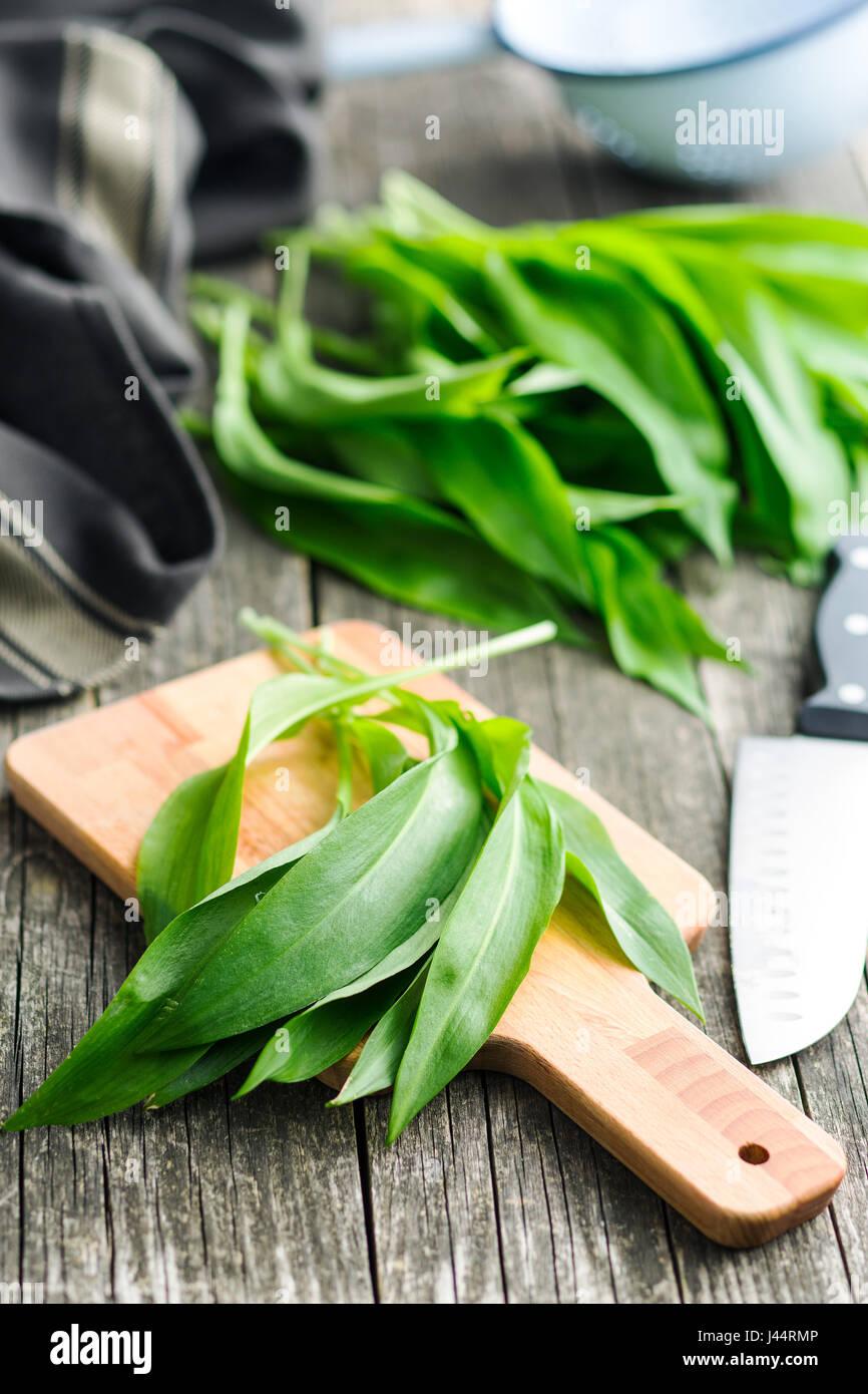 Ramson or wild garlic leaves on cutting board. - Stock Image