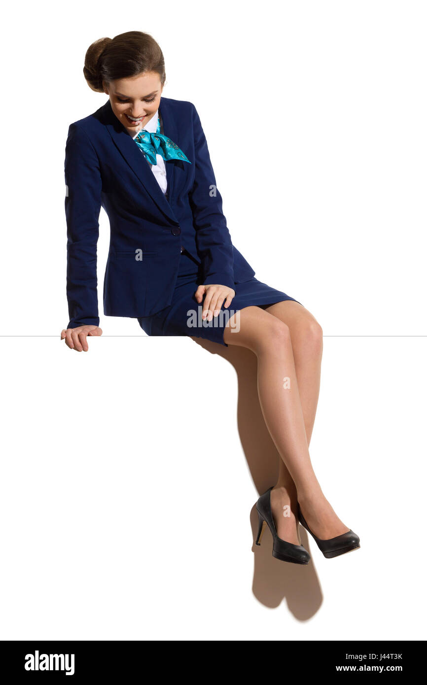 Young woman in blue formal businesswear and black high heels, sitting on a top with legs crossed, smiling and looking - Stock Image