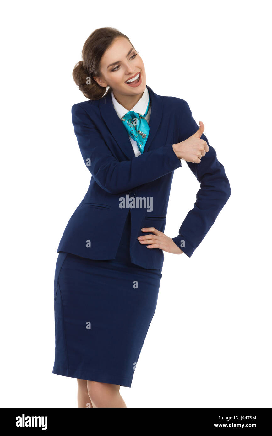 Smiling woman in blue suit and skirt is standing with hand on hip, showing thumb up and looking away. Three quarter - Stock Image