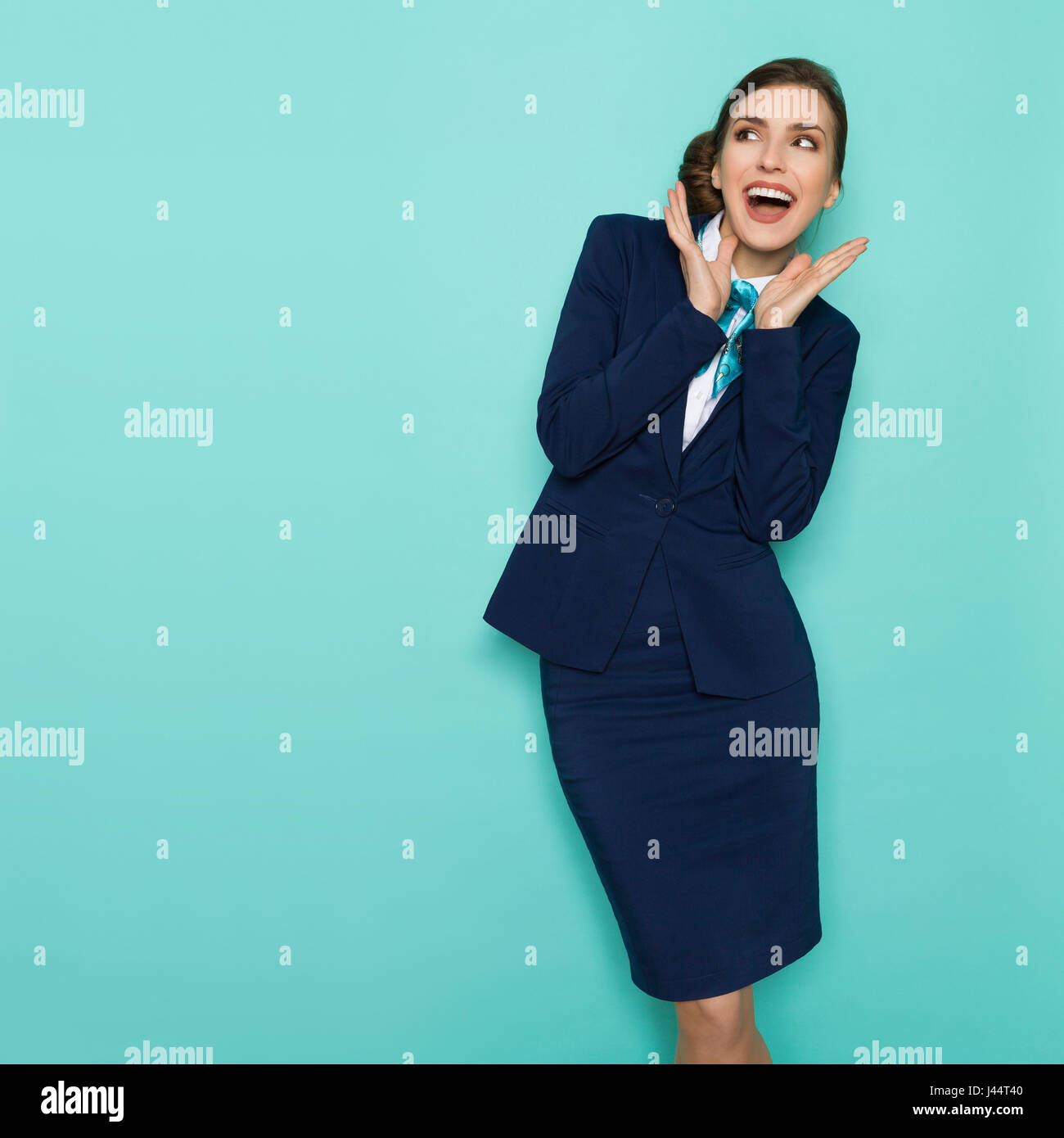 Happy young businesswoman in blue suit and turquoise scarf is standing with hands raised, shouting and looking away. - Stock Image